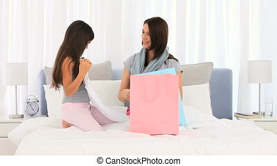 Mother and daughter unpacking shopping bags together