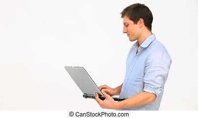 Young man standing up with a laptop