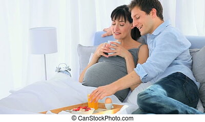 Future parents taking a breakfast on their bed