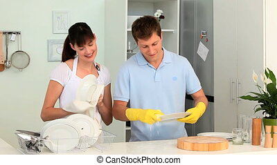 Young couple washing up in their kitchen