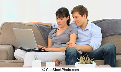 Couple buying something on internet in their living room