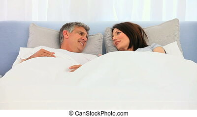 Cute Middle aged person talking in the bed