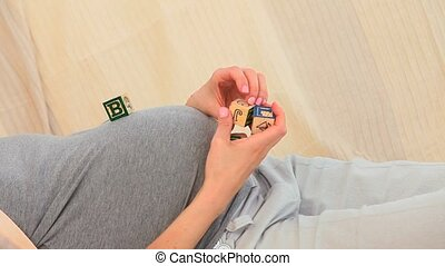 Pregnant woman playing with buidling blocks on a sofa