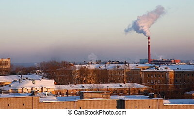 winter urban landscape and pipe with smoke at horizon