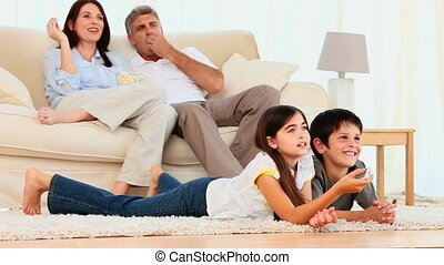 Family watching a movie in the living room