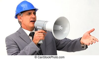 Businessman with a safety helmet and a megaphone against a...