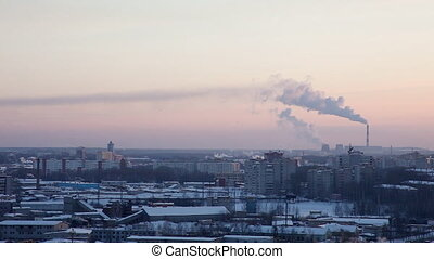 Winter city at sunset in Russia with pipe and smoke