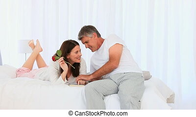 Lovely middle aged couple with a rose in their bedroom