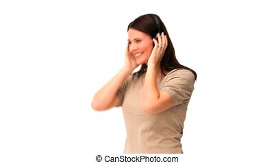 Brunette dancing with headphones against a white background