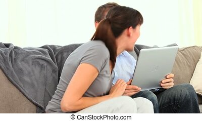 Cute couple having a lot of fun with a laptop