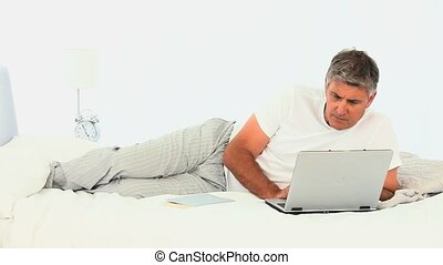 Middle aged man using a laptop in his bedroom