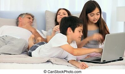 Family on a bed with a laptop