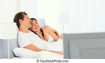 Lovely couple watching tv in their bedroom