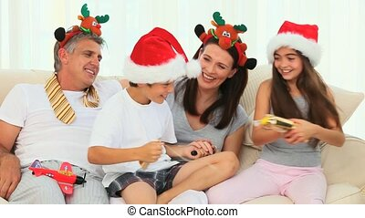 Family during Christmas with crackers on their sofa