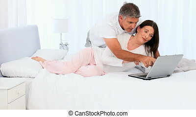 Middle aged couple laughing in front of a laptop on their...