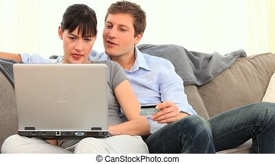 Couple paying something with internet on a couch