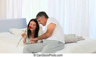 Beautiful Middle agedd couple with a rose in the bedroom