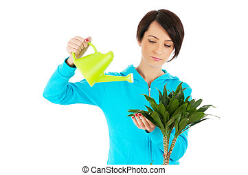 Young woman watering plants isolated on white