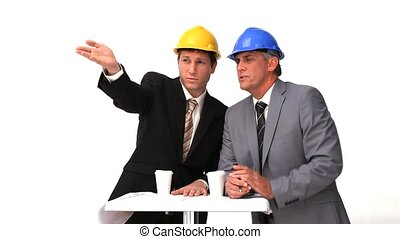 Two architects with safety helmets speaking against a white...