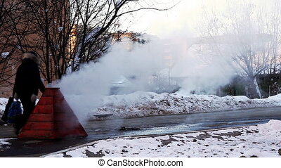 Steam on winter street from water