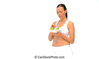 Woman in sportswaer eating a salad against a white...