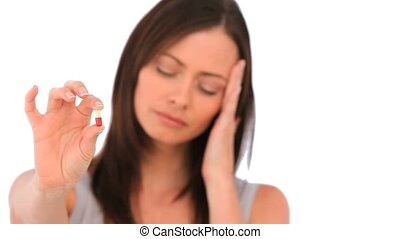 Woman with a headache holding a pill isolated on a white...
