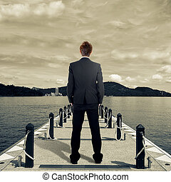 Business man standing on dock near lake.