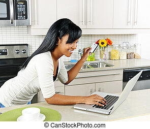 Woman shopping online at home - Smiling black woman online...