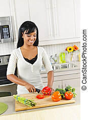 Young woman cutting vegetables in kitchen - Smiling black...