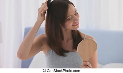 Brunette tidying her hair during the morning in her bedroom