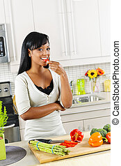 Young woman tasting vegetables in kitchen - Smiling black...
