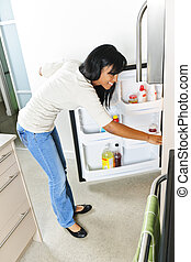 Young woman looking in refrigerator - Black woman looking in...