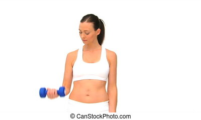 Pretty brunette doing exercise with dumbbells