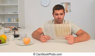 Man reading his newspaper in the kitchen