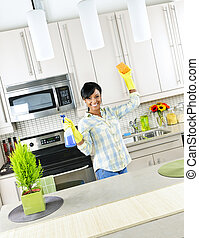Young woman cleaning kitchen - Smiling young black woman...