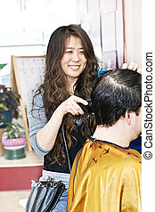 Hairstylist working - Happy hairdresser cutting hair in her...