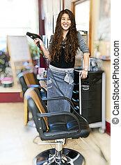 Hairstylist in hair salon - Happy hairdresser holding...