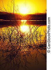 Sunset at lake - A dark moody sunset at a lake with...