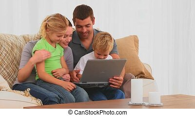 Familly looking at their laptop on the sofa at home