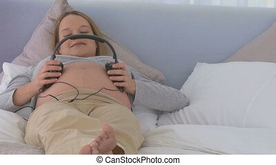 Pregnant woman putting headphones on her belly in the...