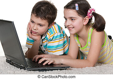 Children discovering laptop - A boy and a girl are studying...