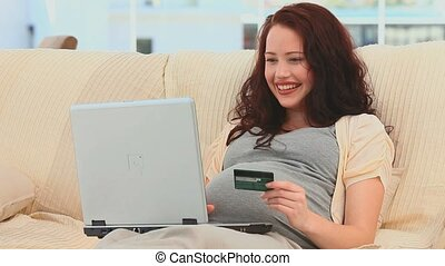 Pregnant woman buying something on