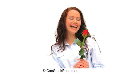 Casual woman smelling a rose against a white background