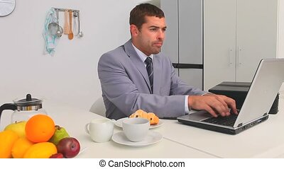 Businessman working during his breakfast with a laptop in...