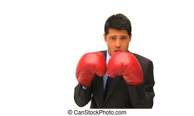 Man dressing in a business suit with boxing gloves against a...