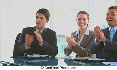 Business people applauding after a meeting in an office