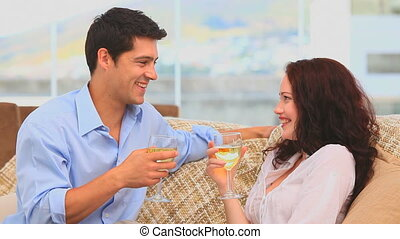 Lovely couple holding glasses of wine on their couch