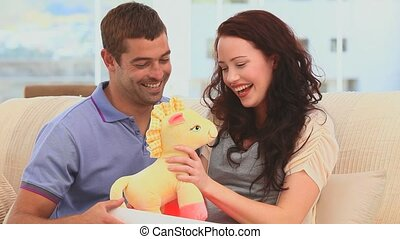 Man offering  a cuddly toy to his wife