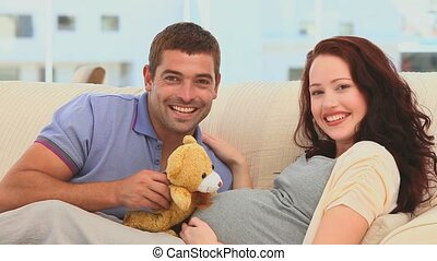 Future parents playing with a teddy bear in their living...