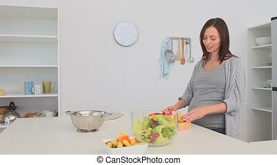 Pregnant woman preparing a salad in the kitchen